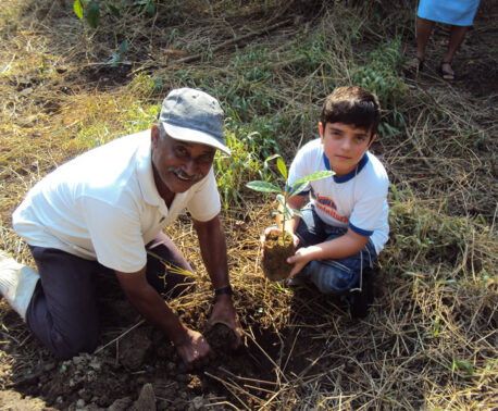 Ranger helps a child plant a tree in the Atlantic Rainforest
