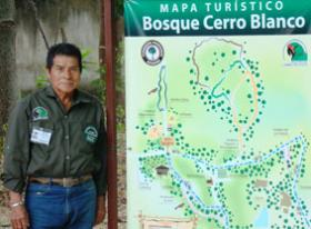Photo of Don Perfecto standing by a map of Cerro Blanco Forest Reserve.