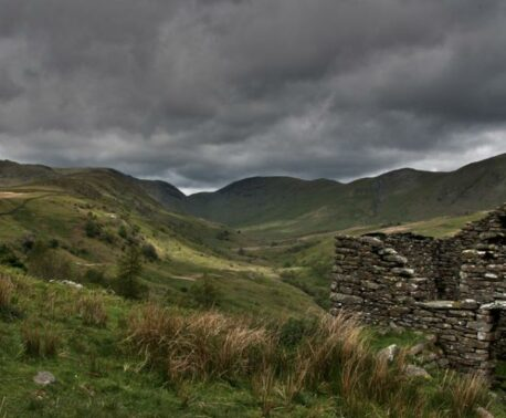 Rolling landscape with storm clouds in the background and stone bothy in the foreground