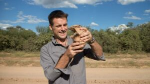 Nick Baker holds up an armadillo.