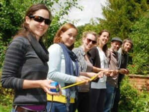 A row of World Land Trust staff hold up a tape measure.