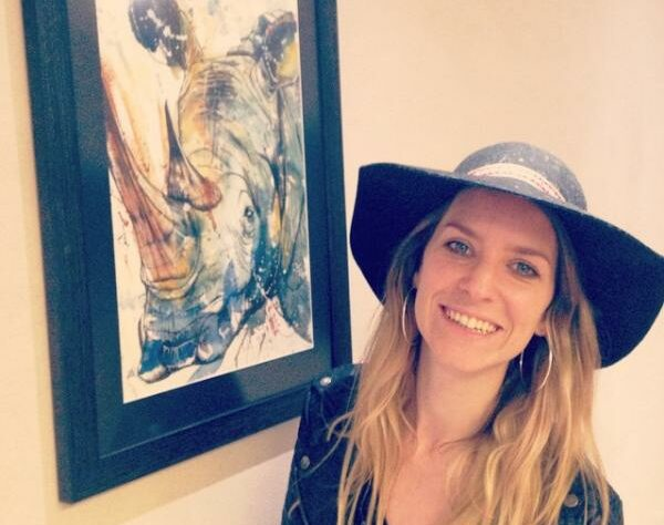 Tori Ratcliffe and one of her paintings of a Rhinoceros.