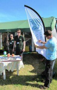 Steve Backshall signs a WLT flag at Camp Bestival.