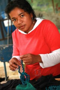 Colombian woman assembling jewellery.