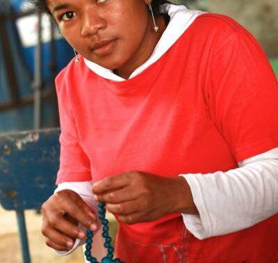 Colombian woman assembling jewellery.