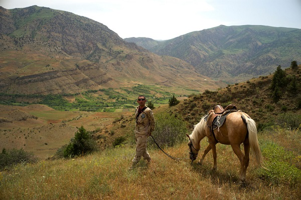 Ranger with horse in Caucasus mountains