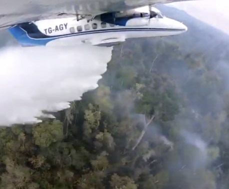 A small plane dropping water on fires in Guatemala. Credit: FUNDAECO
